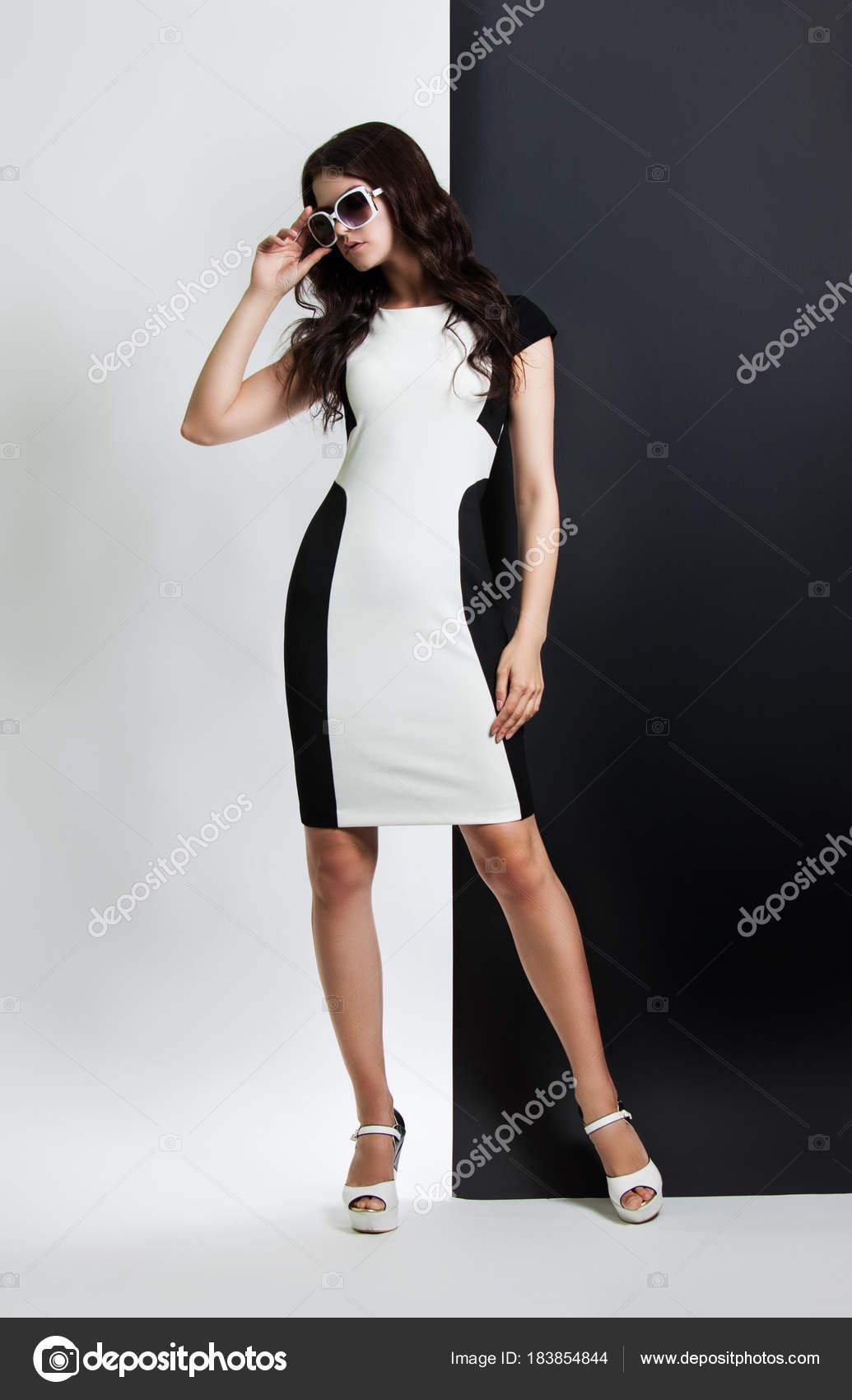 5ff5ceaaa43ea5 Mode portret van een vrouw. mooie meisje in zwart   wit jurk en zonnebril  poseren