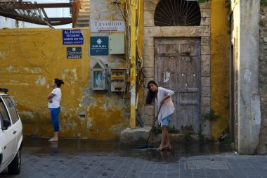 Tyre, Lebanon - June 16, 2017: Women in casual wear cleaning the local street attached to their residence.