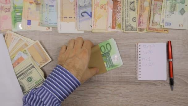 Bankéř počítání euro v jeho kanceláři stolu světových měn kolem něj