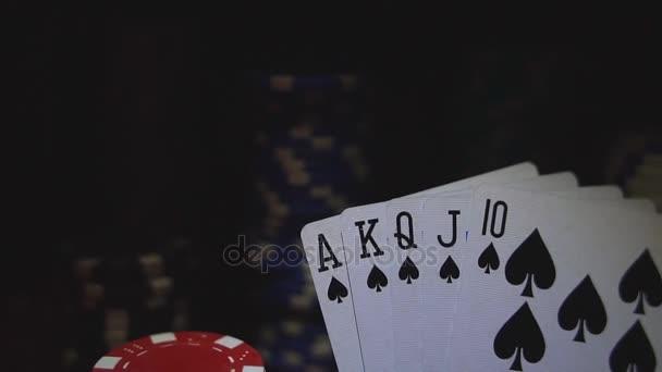 Royal flush na karty a žetony na stole červené casino.