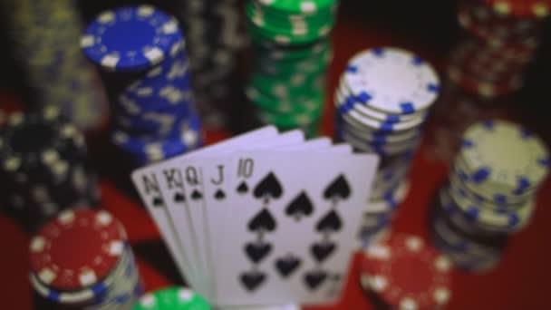 Royal flush del carte e fiches sul tavolo di casino rosso.