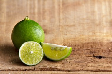 lime and lime slice on wooden background