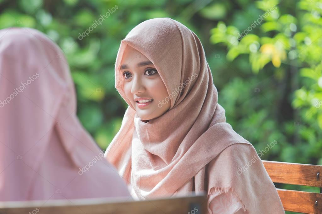 pretty asian muslim woman in cafe with friend