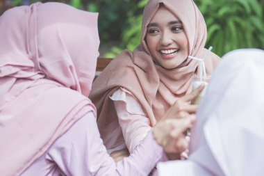 pretty asian muslim woman having fun in cafe together with frien