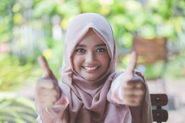 woman with hijab showing thumb up
