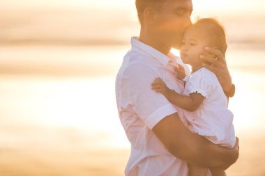 Father and little baby daughter on beach at sunset