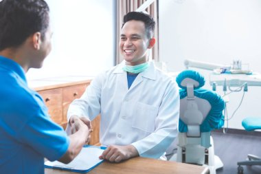 dentist talking to his patient at dental care clinic and shaking