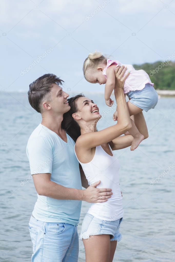 cute little daughter with her lovely parents at the beach