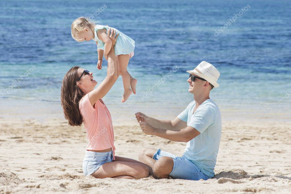 joyful little family having fun together on the beach
