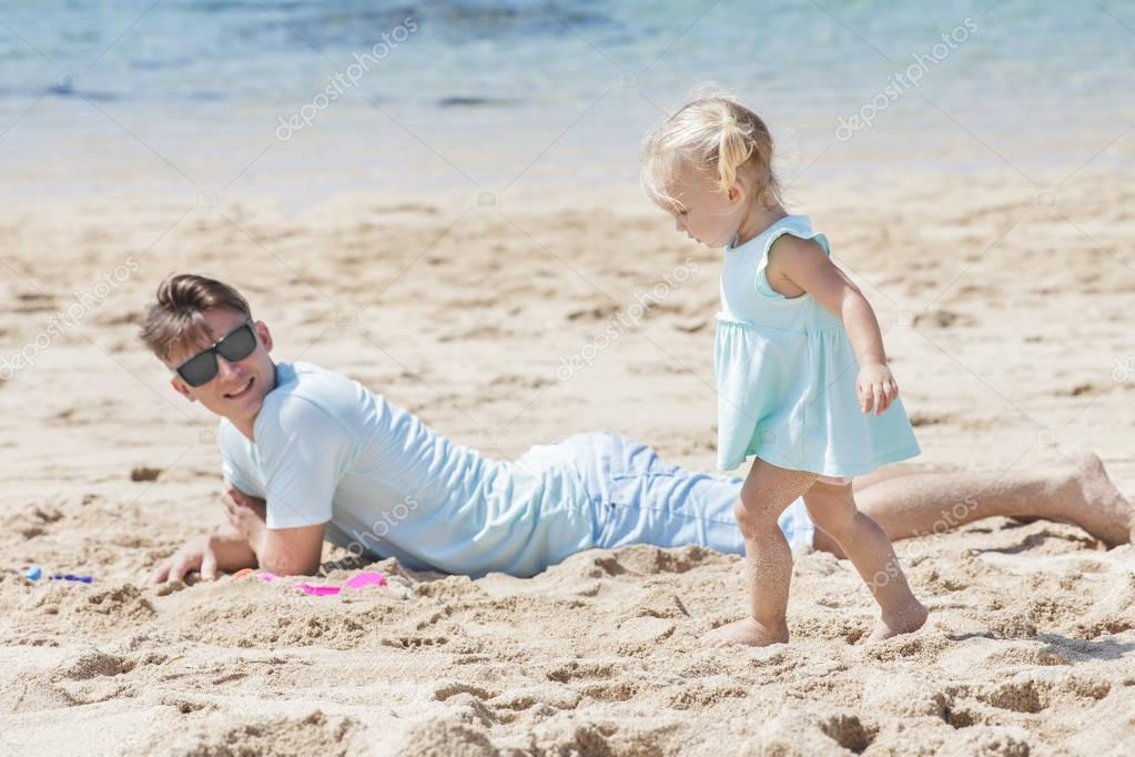 little baby girl playing with her father lying on the sand