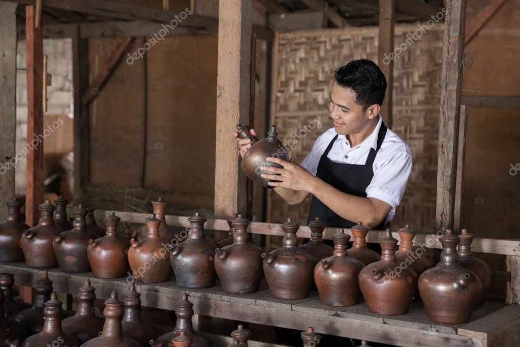 Smiling male potter holding his product in pottery workshop