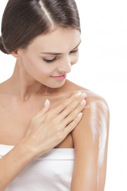 beautiful woman applying body lotion to her arms