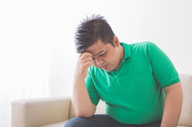 overweight man depress thinking about his weight problem