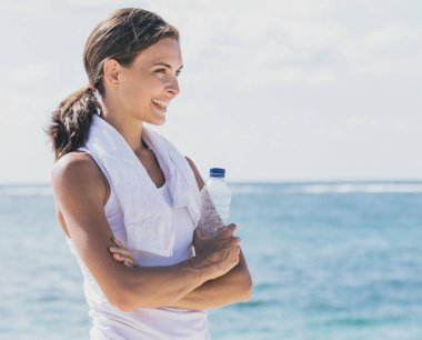 sporty girl smiling while holding a bottle of mineral water