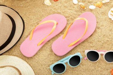 flip flops and sunglasses on beach sands