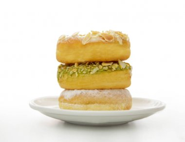 three variant donuts stacked on white plate