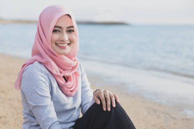 beautiful woman wearing hijab smiling while sitting at the beach