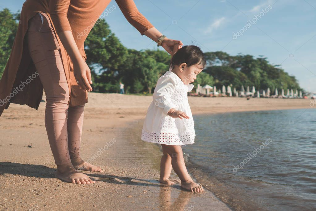 baby trying to walk on beach