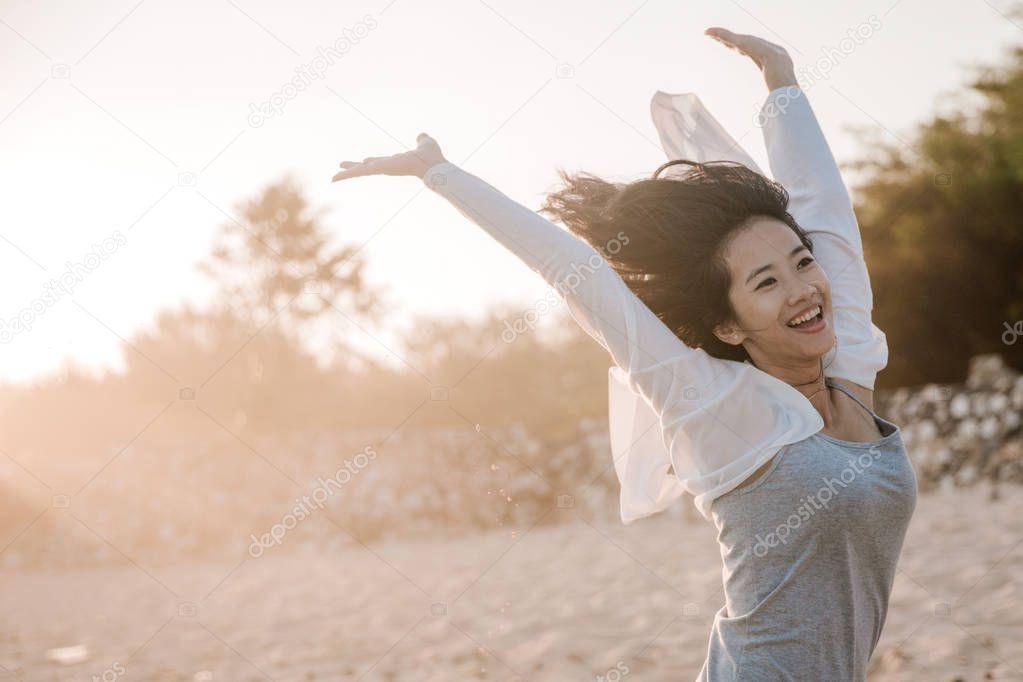 asian woman jumping at beach
