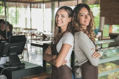 two beautiful female waitress smiling to camera