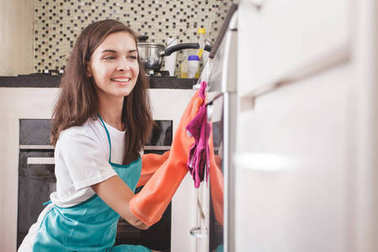 Smiling woman cleaning kitchenware