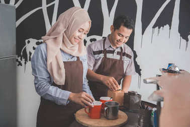 young asian female and male waitress in coffee shop