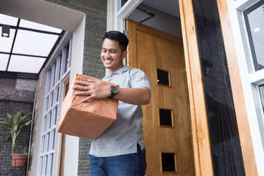 man receiving a delivery box at home