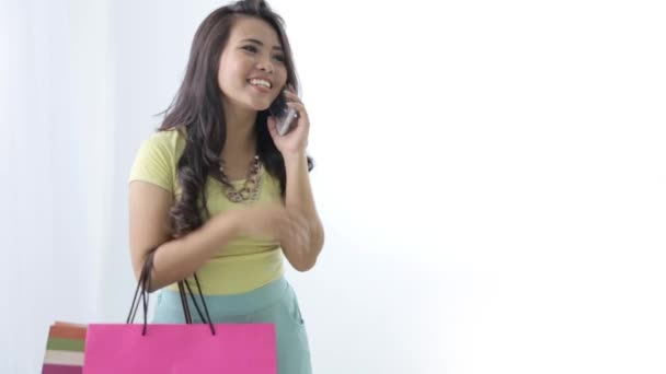 attractive young woman with shopping bag and calling using her m