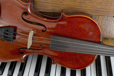 Classical violin on wooden piano keys. Classical violin on piano for music background concept. Holiday concert. Music concept.