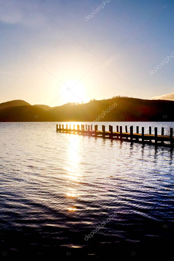 very long wooden jetty, jutting out into a calm blue wooden lake