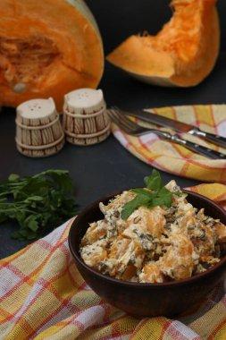 Pumpkin stewed in sour cream in a bowl on a dark background, Healthy breakfast food, Closeup, vertical orientation