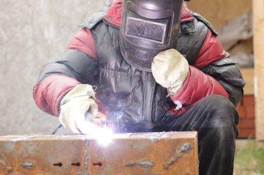 Worker is welding iron steel construction