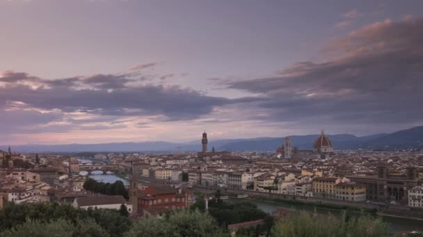 Time lapse of colourful sunset with moving clouds over Italian city skyline of Florence, with cathedral Santa Maria del Fiore, tower Torre di Arnolfo, bridge Ponte Vecchio and river Arno, Tuscany Italy