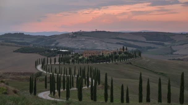 Idő elteltével a birtok Agriturismo Podere Baccoleno naplementekor, a toszkán fák és az út, felhők mozognak, késő nyáron zöld mezők, Olaszország