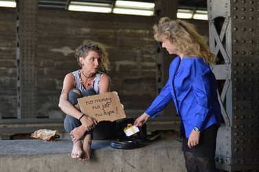 a punk woman sitting under a bridge with a bottle of alcohol in a brown paper bag nearby holding a sign and being startled getting a gift from a businesswoman