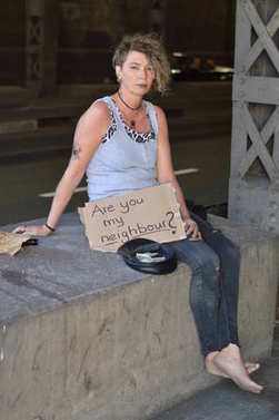 alcohol addicted, homeless woman with emptied bottled alcohol in brown paper bags next to her begging for money holding a sign - are you my neighbor?