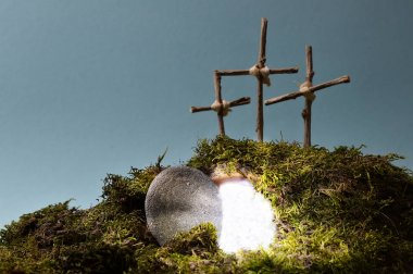 resurrection garden as easter decoration with a stone near the empty tomb filled with blinding light and three crosses on a hill above