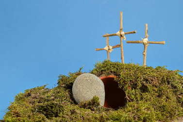 resurrection garden as easter decoration with a stone near the empty tomb and three crosses on a hill above