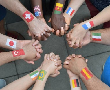 International brothers and sisters standing in a circle together and holding hands with flags painted on their arms