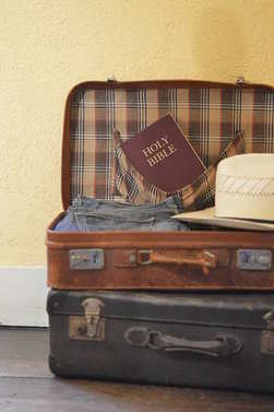 Suitcase filled with clothes, hat and a bible for a mission journey