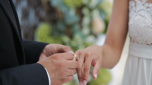 La sposa e lo sposo scambio di fedi nuziali su uno sfondo di composizione nel fiore. Lo sposo mette lanello sul braccio del suo primo piano sposa. Giorno del matrimonio