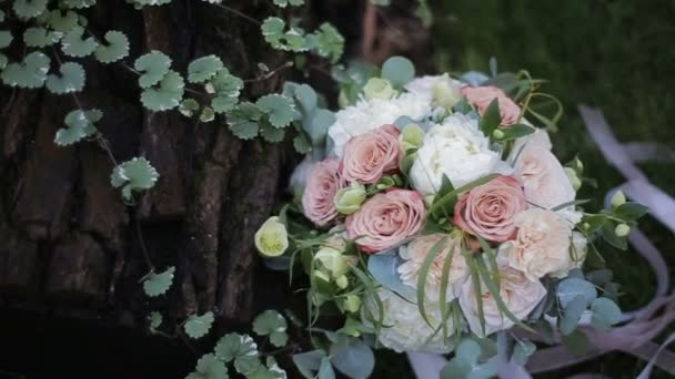 Beautiful wedding bouquet of white roses and creme carnations on the grass near an oak tree.