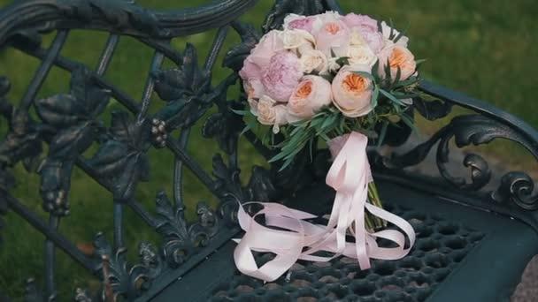 Svatební kytice z růží a pivoněk na staromódní černé kovové lavice zdobené kovové grapevine. Svatební kytice různých květin. Kytice krásná růžová, krémová a bílé květy