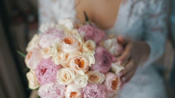 Braut hält ein Brautstrauß aus Rosen und Pfingstrosen. Brautstrauß ...