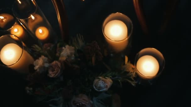 Burning candles with beautiful bouquet of different flowers near a chair.