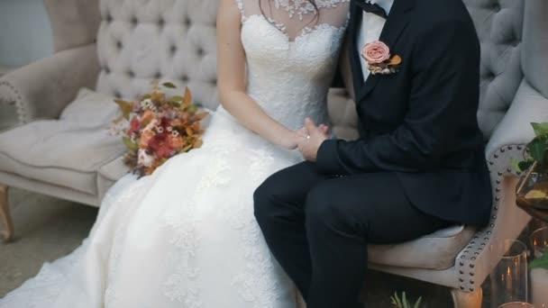 Svatební pár, držení rukou, šťastný ženich a nevěsta krytý na gauči. Mladý pár v lásce nevěsty a ženicha, svatební den