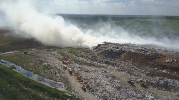 Garbage dump pollutes the environment. Strong wind rises toxic smoke of burning garbage into the air.