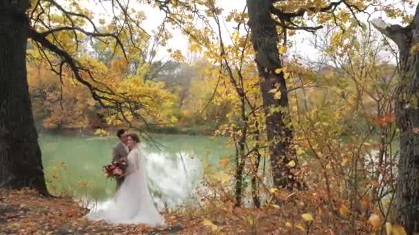 Groom and bride hugging near a lake in autumn forest among Colored fall trees. Young attractive Happy loving newlyweds in a park in Slow motion.
