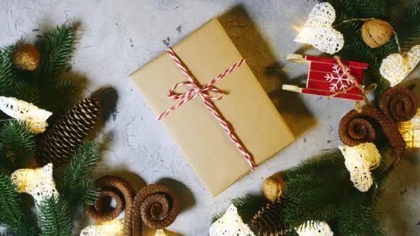 Asztal ünnepi játékokkal és karácsonyi dekorációval. A női kezek felvesznek egy lezárt ajándékot az asztalról. Kúp alakú dió fenyő és fenyő gyertya ágak. Közeleg az újév. Lassú mozgás a fenti nézetben
