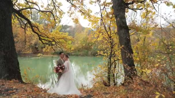 Wedding in the woods in nature. Groom and bride hugging near a lake in autumn forest among Colored fall trees. Young attractive Happy loving newlyweds in a park in Slow motion.